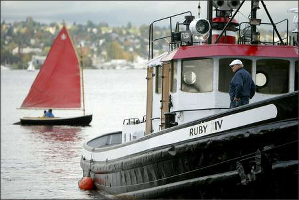 A sailboat passes behind the Ruby XIV, a 65-foot tugboat built in 1945, during the Classic Workboat Show, sponsored by Northwest Seaport and The Center for Wooden Boats, at Lake Union Park in Seattle. The event featured several workboats, mostly tugs from the '20s, '30s and '40s.