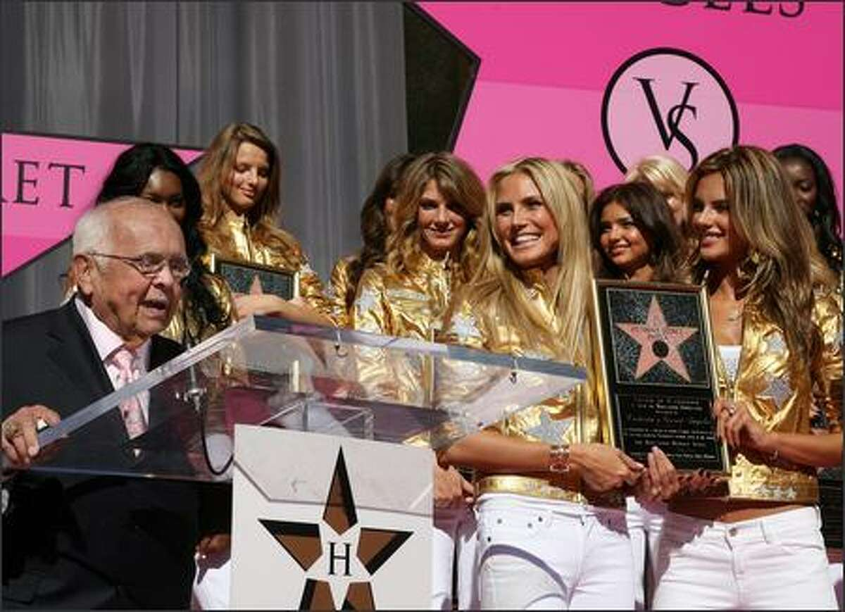 Victoria's Secret Angels listen as Honorary Mayor of Hollywood Johnny Grant (L) delivers a speech on the Hollywood Walk of Fame in front of the Kodak Theater on Hollywood Boulevard after that were honored by a star to celebrate the 25th anniversary of Victoria's Secret 13 November 2007 in Hollywood, Calif.