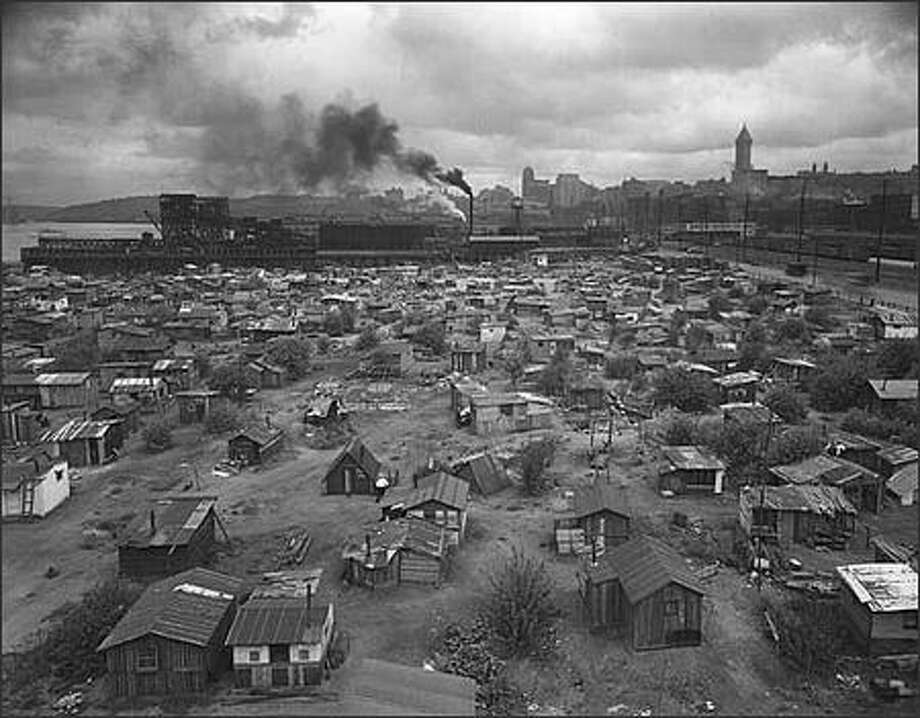 During the hard times of the 1930s economic depression, many unemployed and homeless people settled just west of where Seattle's sports stadiums now stand. They built ramshackle houses out of scrap material and elected their own mayor. The area was nicknamed Hooverville or Hoover City by people who blamed President Herbert Hoover for causing the Depression.   This 1933 photo, taken at Seattle's Hooverville, shows the small houses scattered between the roadway and the waterfront. (Webster & Stevens)
