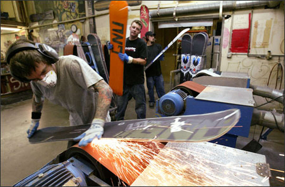 Jim Ayo grinds imperfections out of a snowboard at the Mervin Manufacturing plant on West Commodore Way in Seattle on Tuesday.