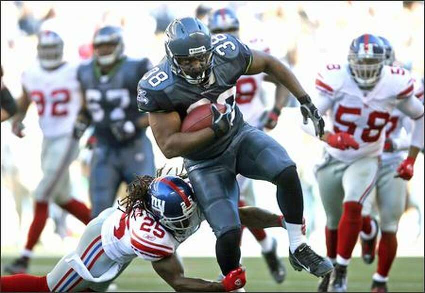Seattle Seahawks fullback Mack Strong makes 14 yards before being brought down by New York Giants R.W. McQuarters at Qwest Field on Saturday, Sept. 23, 2006. (Mike Urban/Seattle Post-Intelligencer)