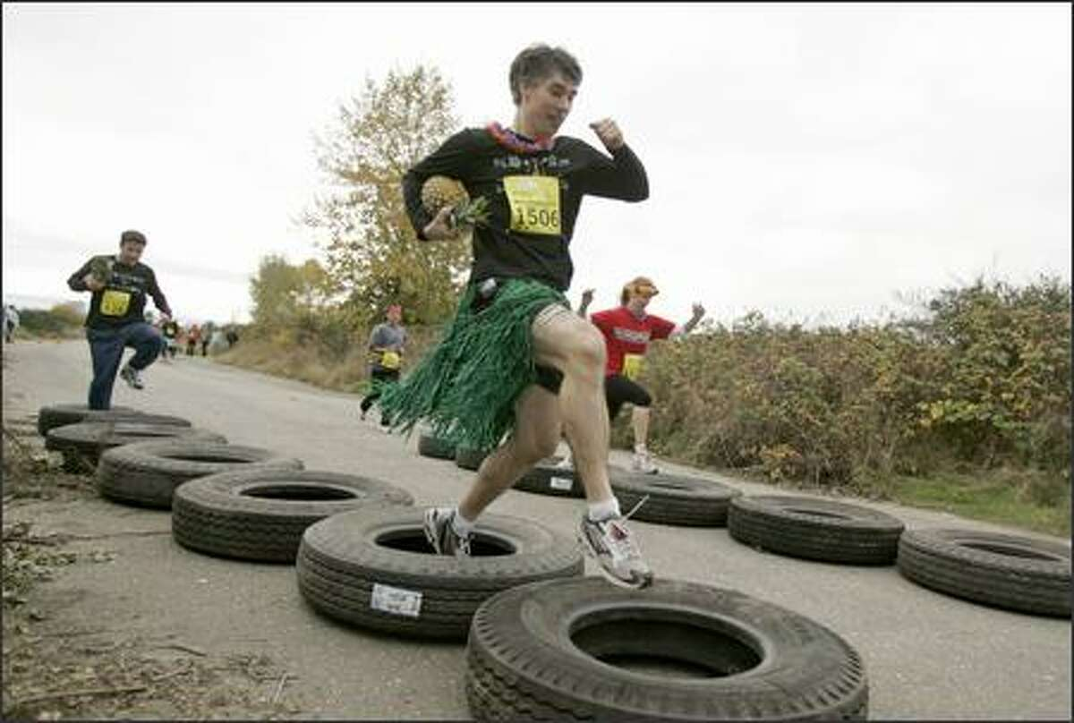 Tom Dickerson of the Kanapali Kickers team runs through tire obstacles during the Winter Pineapple Classic, a 5-kilometer, Hawaiian-themed race through an obstacle course to raise money for leukemia and lymphoma research, at Magnuson Park in Seattle.