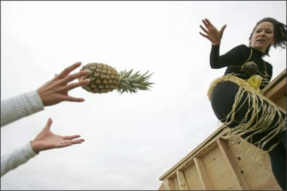 Members of Team Komonawannaraceyou negotiate a wooden wall while protecting the team pineapple.