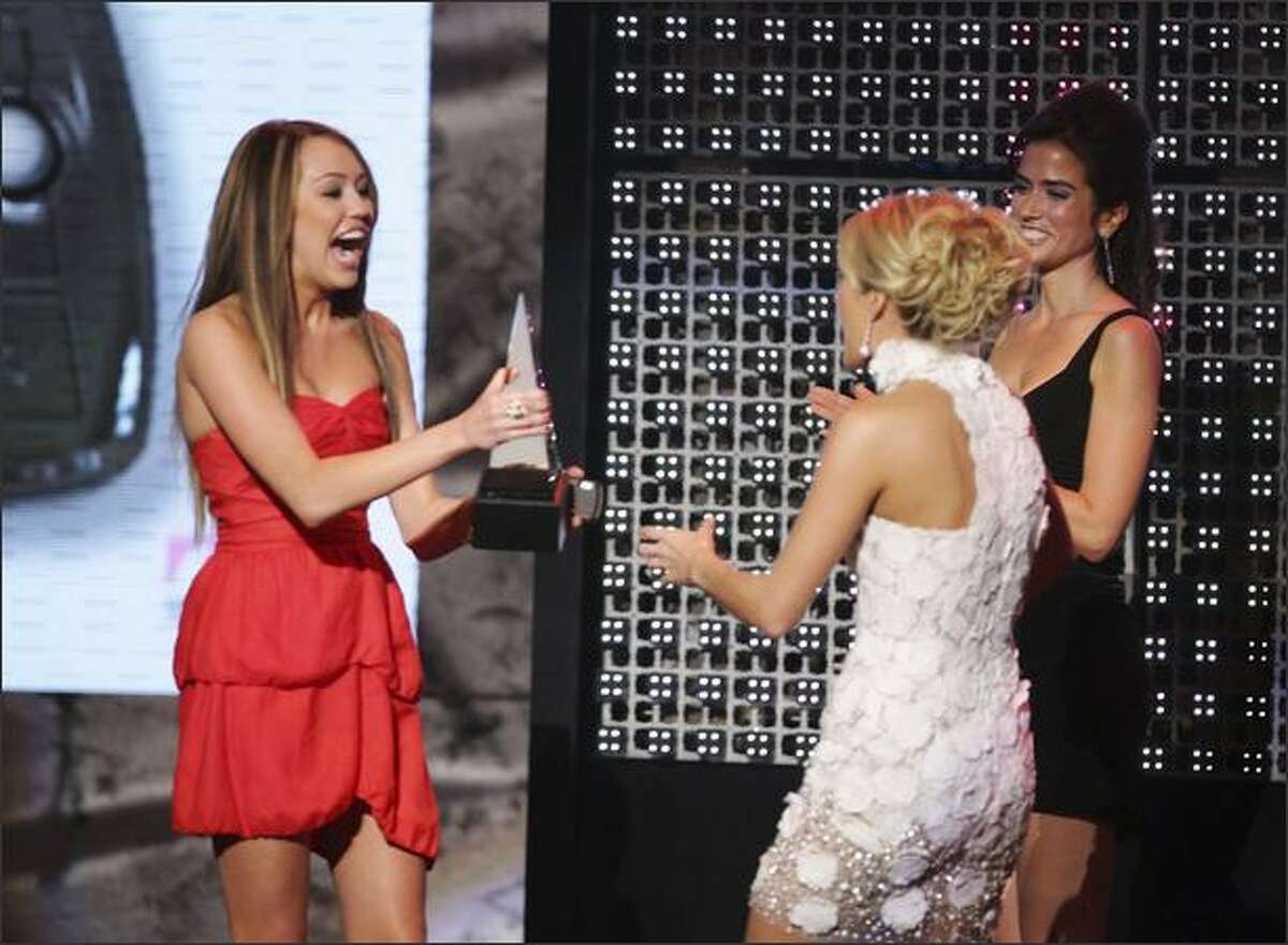 Miley Cyrus, left, presents Carrie Underwood with the T-Mobile Text-In Award during the 2007 American Music Awards.