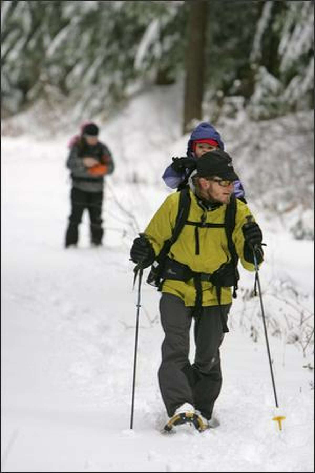 """Matthew Grummer, of Seattle, carries his daughter Araiya, 2, while snowshoeing near Snoqualmie Pass. Grummer, who was with his wife and other daughter, said that they """"came to give their kids a sense of adventure."""""""