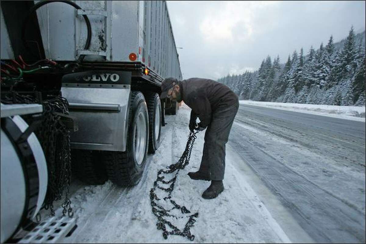 Dan Myers, a trucker from Outlook, Wash., puts on snow chains in Snoqualmie Pass on his way back home from a drop in Tukwila.