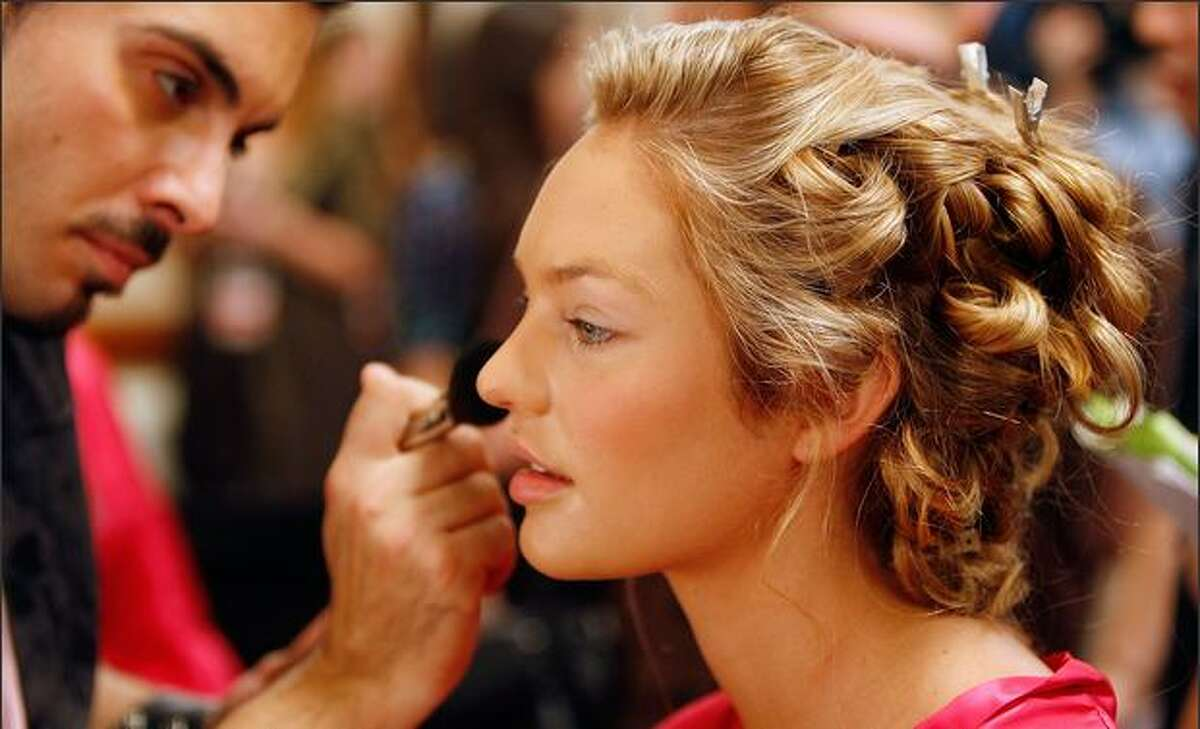 Model Candice Swanepoel prepares backstage before the Victoria's Secret Fashion Show at the Renaissance Hotel in Hollywood, California.