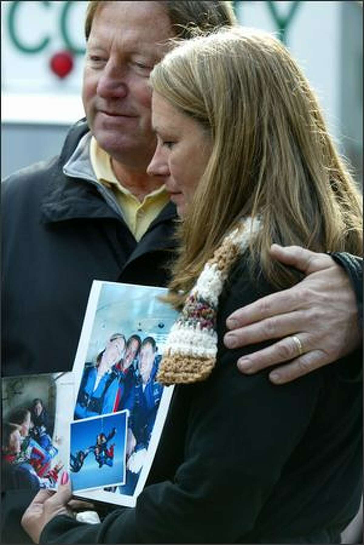 Wanda Craig, mother of Casey Craig, who died in the crash near White Pass, holds a family photo of Casey, his brother Kelly and sister Ivy Green as her husband and Casey's father, Dennis Craig, offers support.