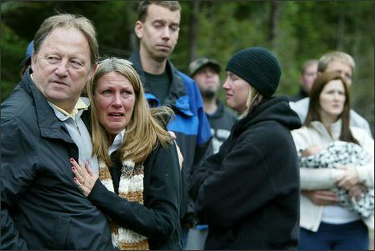 Family and friends of Casey Craig watch and react as a King County sheriff's helicopter lifts bodies from the crash site of a small plane near White Pass.