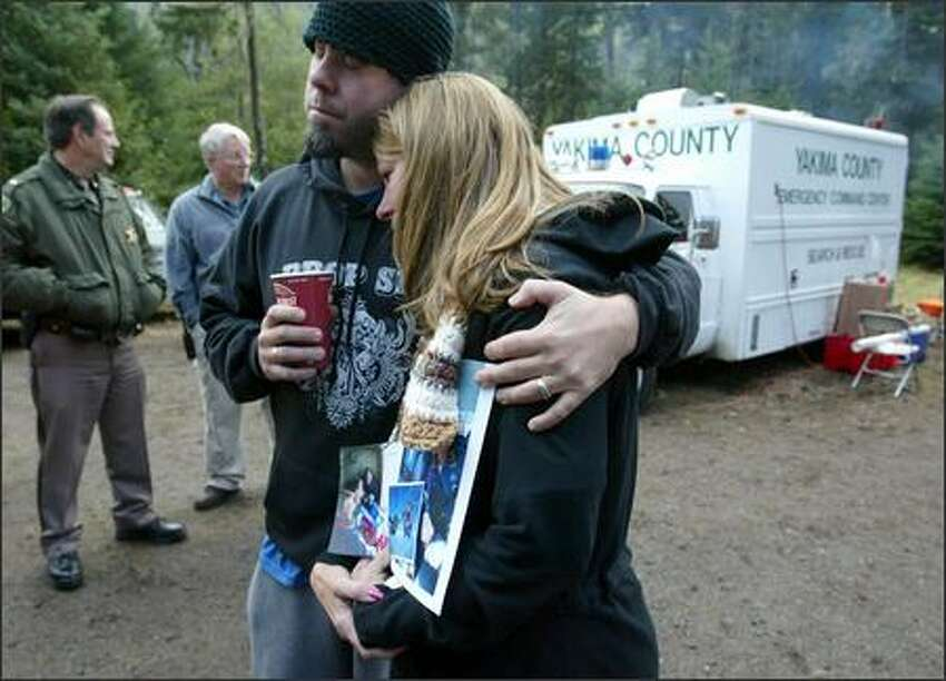 Wanda Craig, mother of Casey Craig, is comforted by Nate Jackson, a family friend, at the staging area for search and rescue.