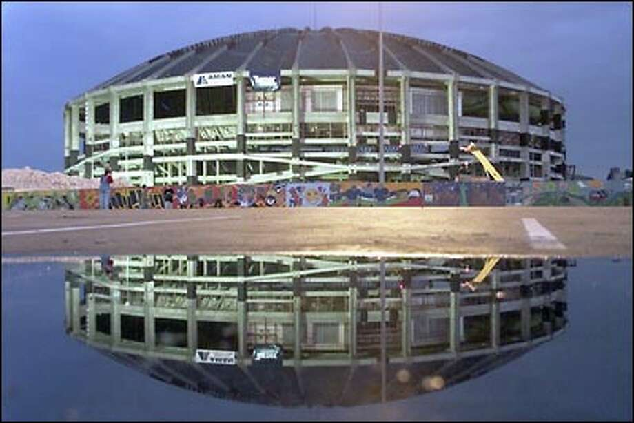 Last look:  The Dome is reflected in a puddle as dawn breaks on Sunday, March 26, a few hours before the stadium's destruction. Photo: Mike Urban, Seattle Post-Intelligencer