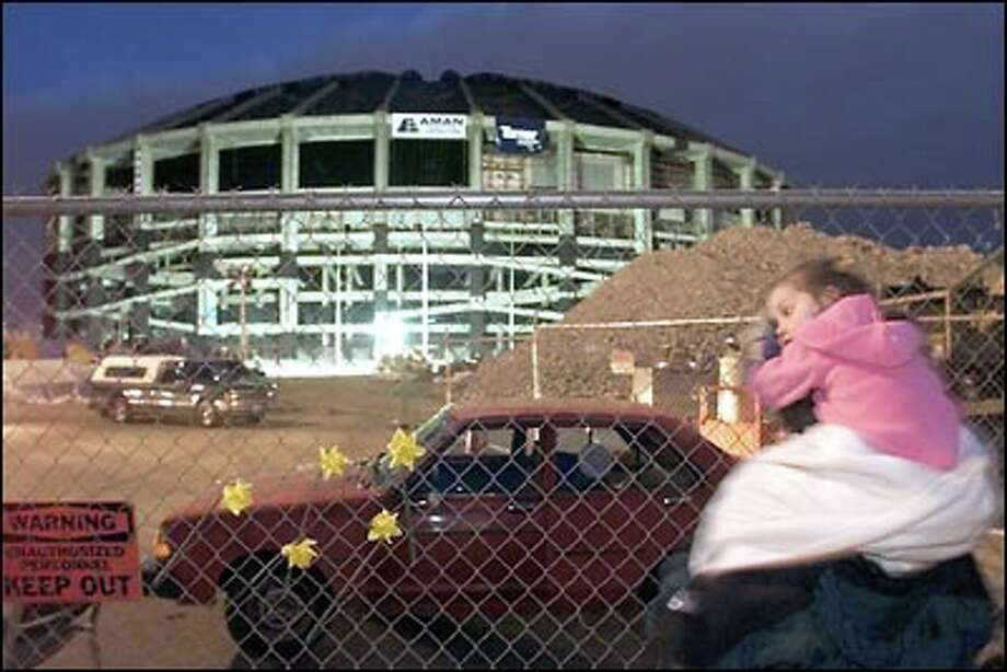 Spectators began lining up before dawn at numerous vantage points around the city.  Here, onlookers took a last glance at the Kingdome before surrounding streets were closed to the public. Photo: Mike Urban, Seattle Post-Intelligencer