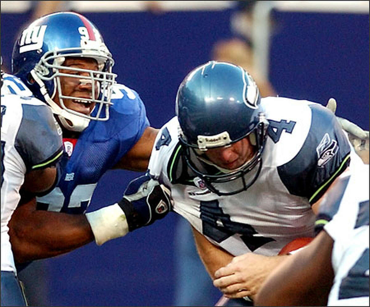 Giants defensive end Michael Strahan grabs Seahawks quarterback Trent Dilfer for one of New York's two sacks. The Giants held Dilfer to 118 yards passing, 4.7 yards per attempt.