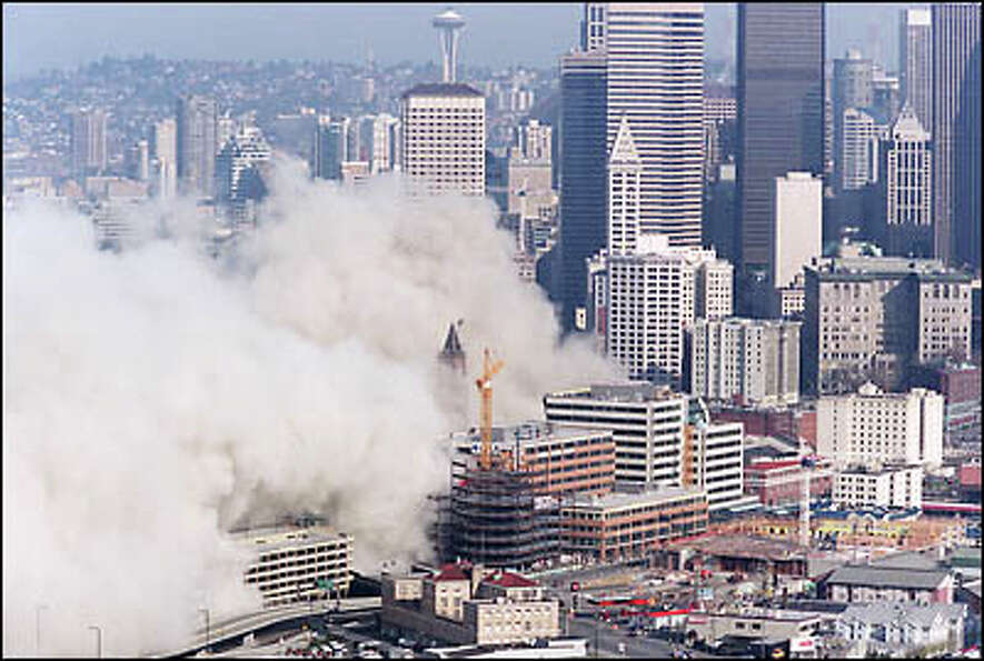 A huge cloud of dust moves toward downtown after the Kingdome's implosion. Afterward, work crews toi