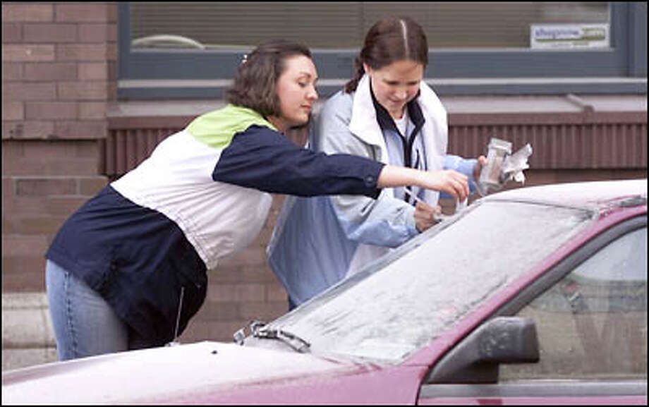 Amy Allred and Julie Moenkhaus scrape Kingdome blast dust from a windshield.  The pair, who watched the implosion from the 64th floor of the Bank of America Tower, plan to make souvenir snowglobes from the dust they gather. Photo: Mike Urban, Seattle Post-Intelligencer