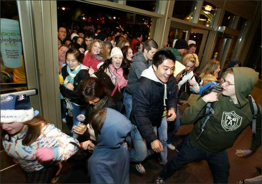 "Customers burst through the doors as Alderwood Mall opens at 12:01 a.m. the day after Thanksgiving for ""Black Friday"" sales. Photo: Joshua Trujillo, Seattlepi.com"
