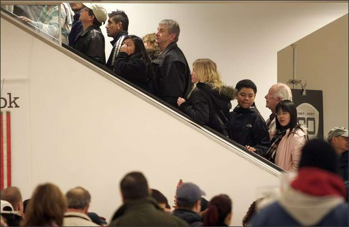 Crowds rush for the escalators inside Sears at Westfield/Southcenter on Black Friday.