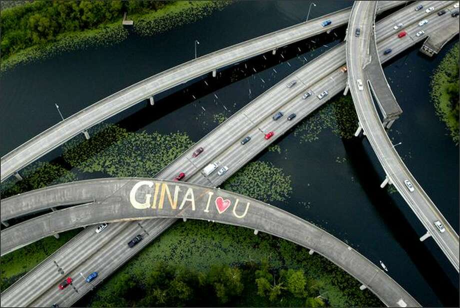 """A message of love to an unknown """"Gina"""" is scrawled across the lanes of an overpass on state Route 520 at the Arboretum in Seattle. The message was painted on an unused ramp on the highway in the serene park. The painter and the recipient of the message are mysteries.Trujillo:When flying into Sea-Tac Airport I saw this scene during the approach. I was in a commercial airliner and had only a point-and-shoot camera. The following morning I persuaded an editor to let me charter a helicopter to photograph someone's message of love -- along with some other aerial photos we needed for other stories. After the photo was published, it became one of the most viewed items on seattlepi.com that day, a rare occurrence for a single photograph. In fact, readers debated on a soundoff board in their unique fashion, wondering if it was an enchanting message of love or illegal graffiti. But even more interesting was the public interest in who Gina was. It became the subject of a talk radio show and was discussed on blogs. Someone even wrote a ballad about the message of love to Gina. Photo: Joshua Trujillo, Seattlepi.com"""