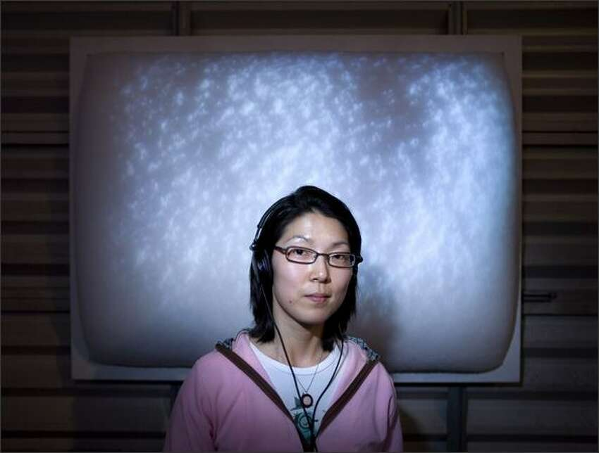 Artist Susie J. Lee, with headphones from her piece, poses in front of her work titled