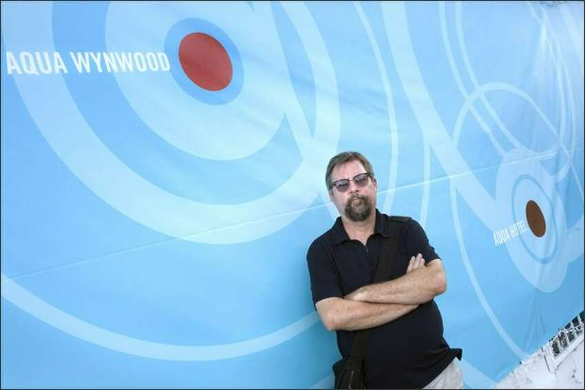 Dirk Park, one of the organizers of the Aqua exhibitions, poses in front of a sign for Aqua Wynwood and Aqua Hotel exhibition spaces at the Aqua Wynwood location in Miami, Fla. Photo by Jacek Gancarz