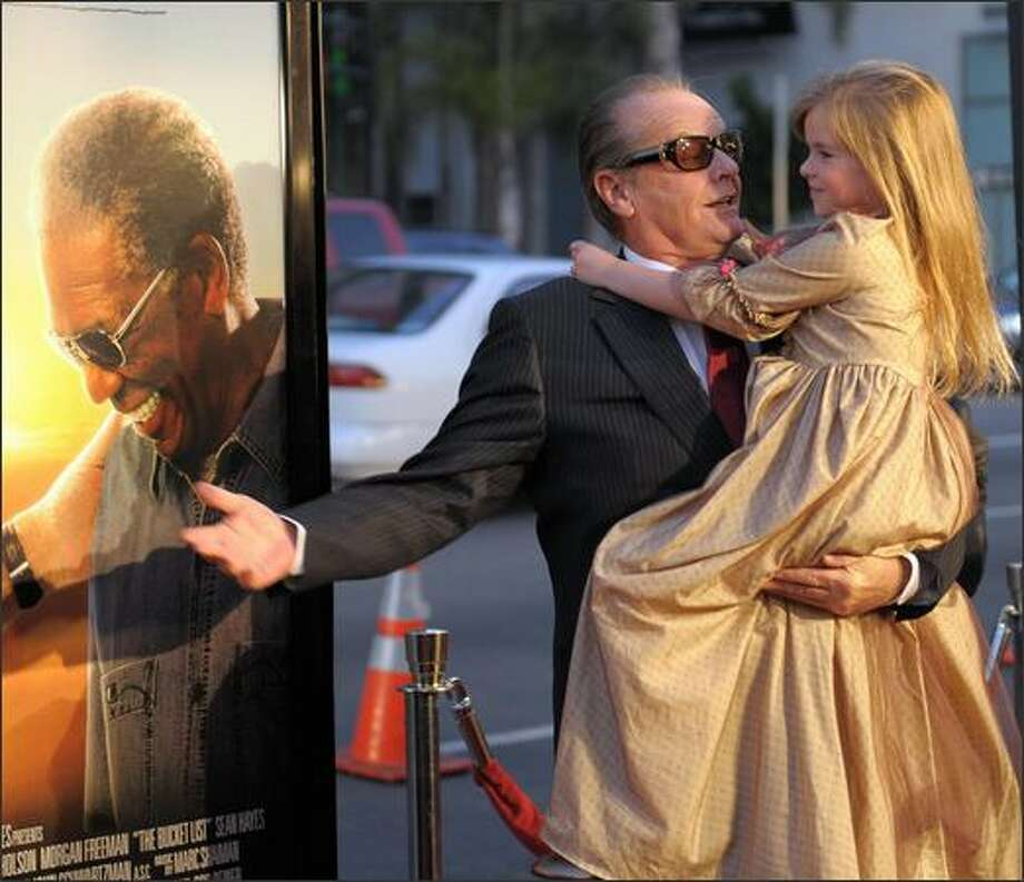 """Actor Jack Nicholson hugs actress Taylor Ann Thompson as he arrives at the premiere of """"The Bucket List"""". The film is the story of two terminally ill men, Jack Nicholson and Morgan Freeman, escape from a cancer ward and head off on a road trip with a wish list of to-dos before they die. Photo: Getty Images"""