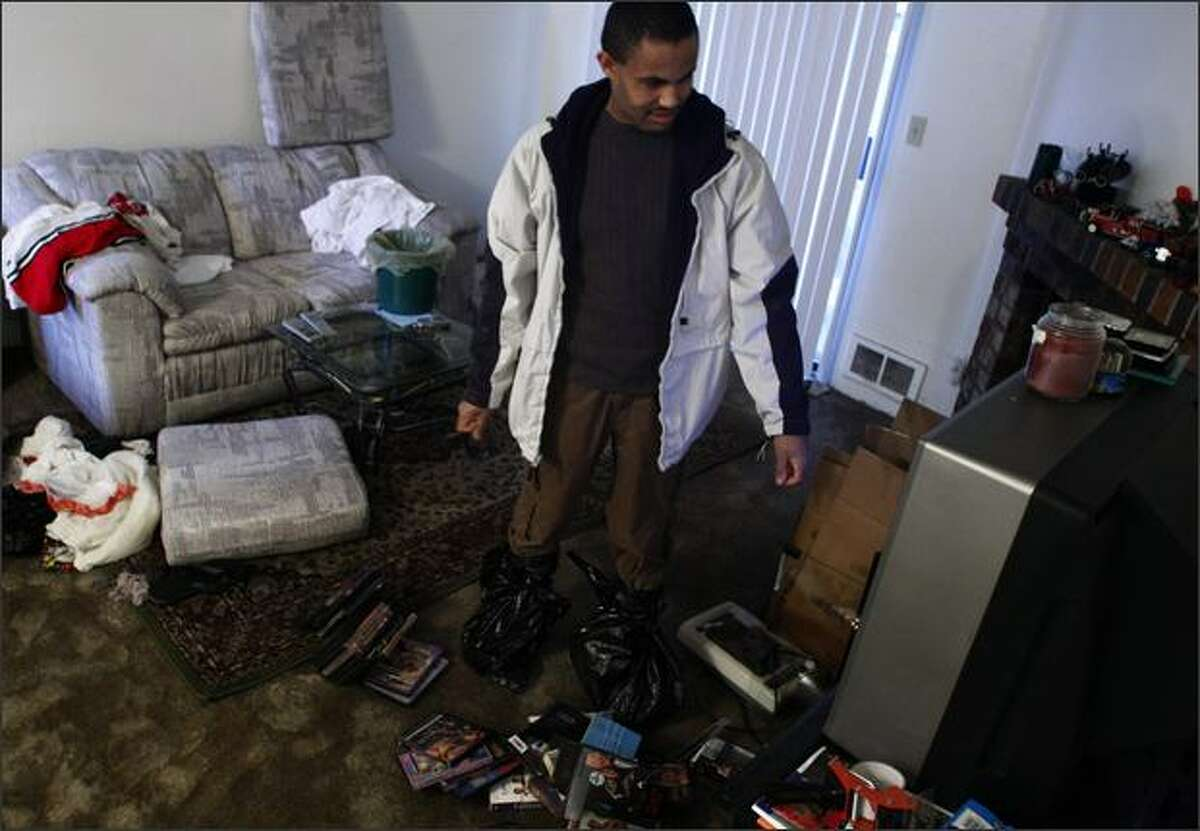 Wearing boots made from plastic bags to protect his shoes, Seife Worede smiles to find that his television still works while sorting through the damage at his unit at the Jackson Greens Apartments at 15th Ave. NE and NE 135th St. in Seattle. The men had been packing to move to another apartment in the complex prior to the flooding Monday.