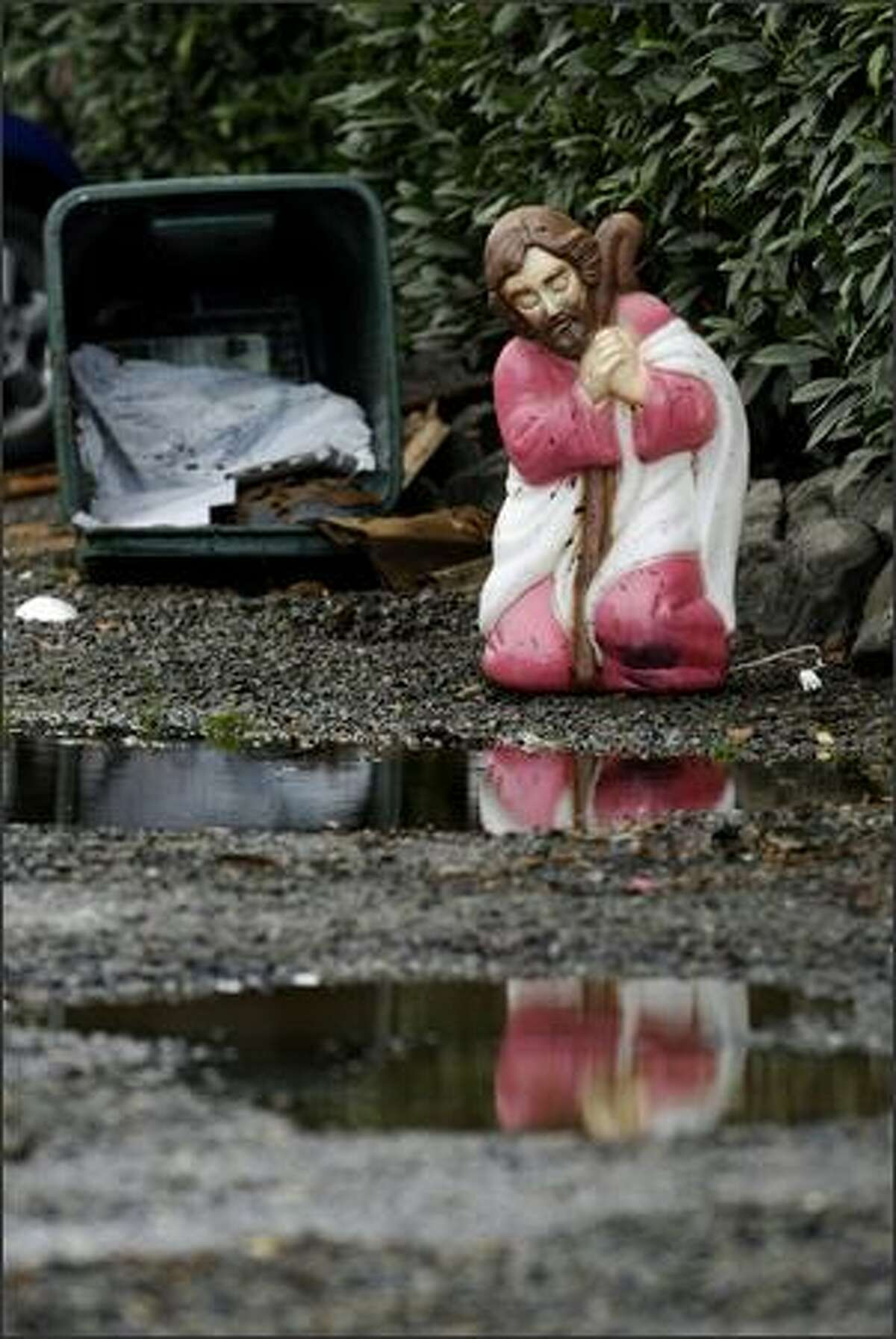 A plastic Joseph kneels near puddles along N. 107th St. between Midvale Ave. N. and Stone Ave. N. after the nativity scene was dispersed by flood waters Monday.
