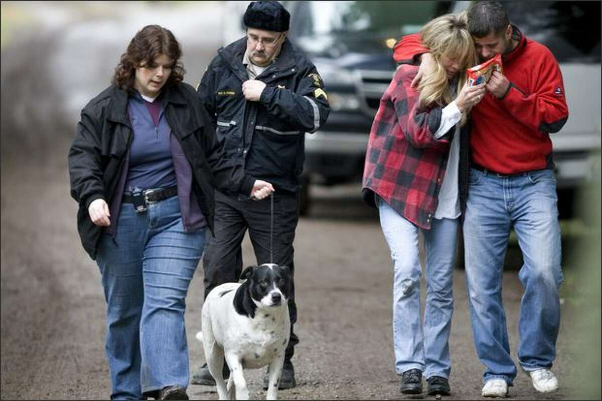 King County Sheriff's Office Detective Robin Cleary leads a dog followed by King County Animal Control Officer Sgt. Steve Couvion and relatives Mary and Ben Anderson near the family's home near Carnation. Six people were murdered in the house on Christmas Eve 2007.