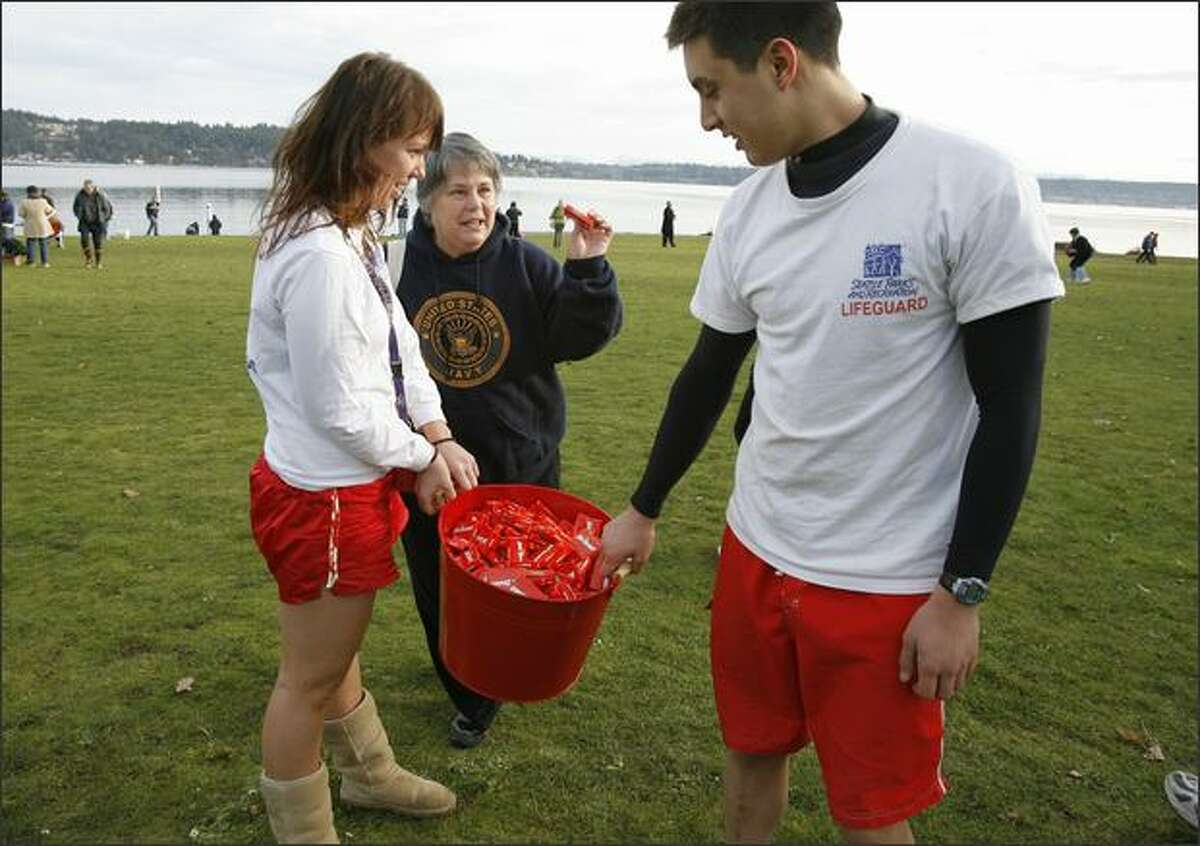 Seattle Parks Lifeguards Caroline Marshall, left, and Taylor Martin right, hand out Hot Tamales to participant Mary Boles-Hall, center, and her husband, Bernie Hall, before the Sixth Annual Polar Bear Plunge on Tuesday at Matthews Beach Park in Seattle.