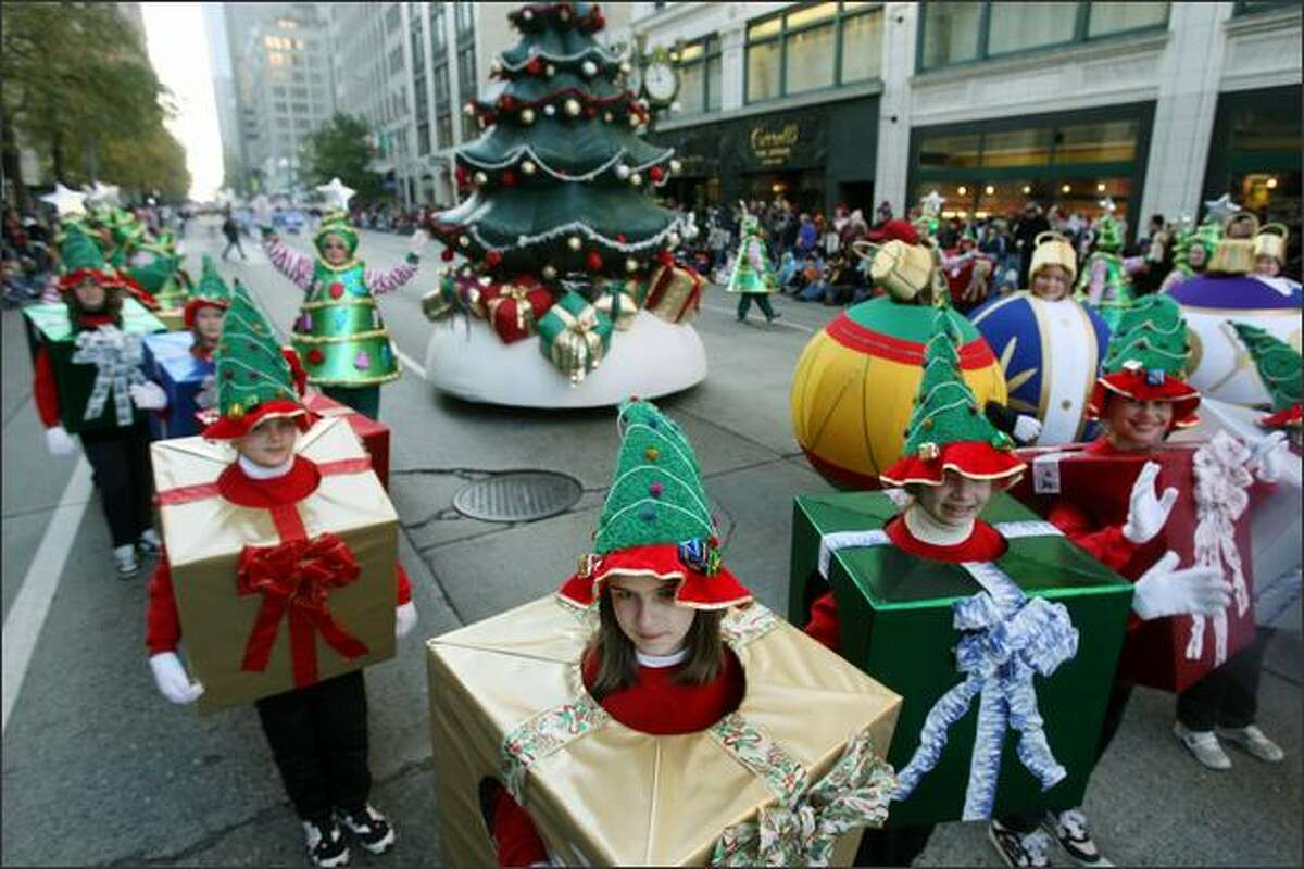 Volunteers of Friends of Macy's participate in the Macy's holiday parade in downtown Seattle.
