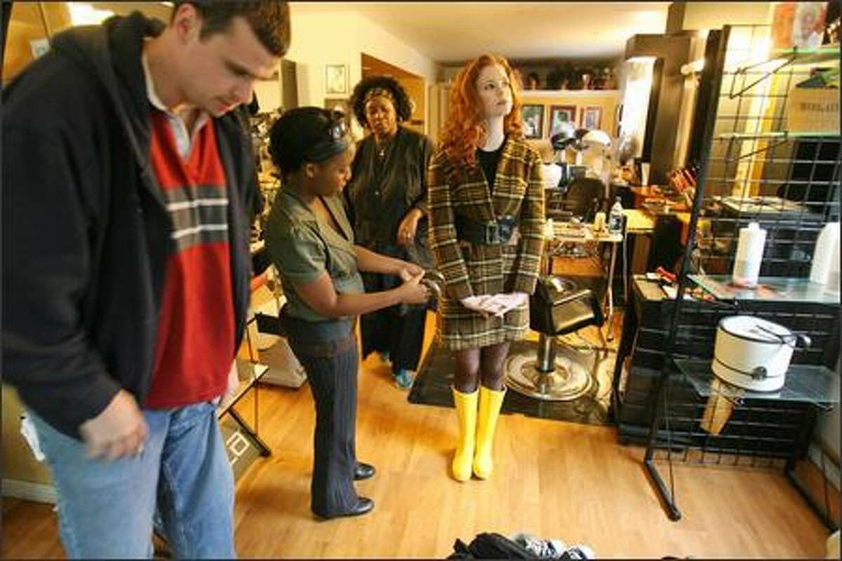 Sylist assistant Chelsea Banks (center left) and stylist Kay Matthews (center left) helps Claire Nelson (center) prepare for a modeling shoot with photographer Ryan James Hunt (left) at the Washington Park Arboretum in Seattle on Oct. 1.
