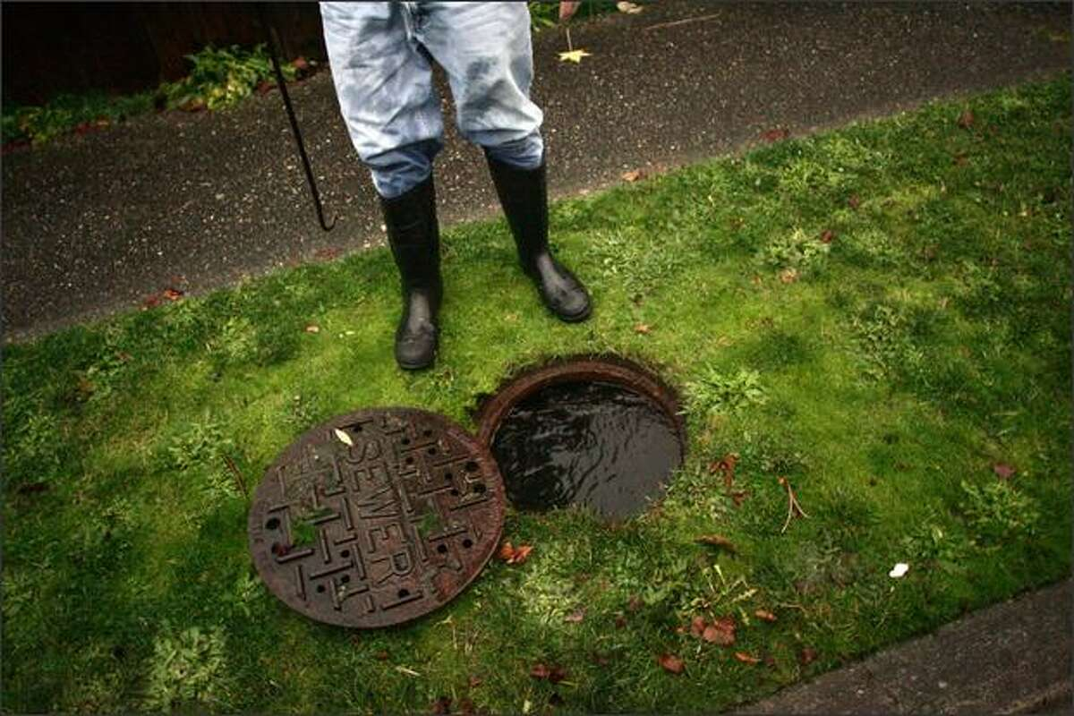Dave Barton stands over a sewer line that he opened after heavy rains caused major flooding at his home in Greenwood in Seattle.