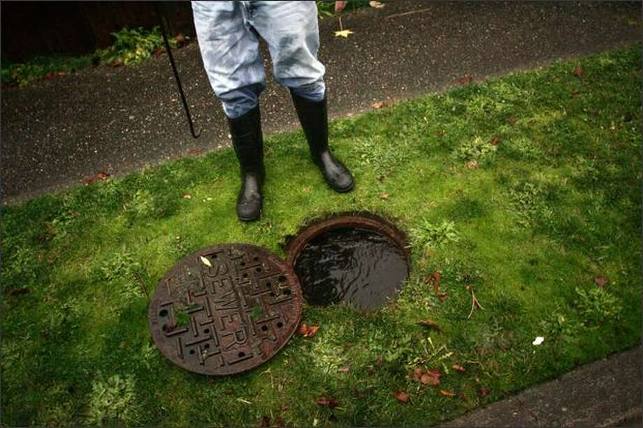 Dave Barton stands over a sewer line that he opened after heavy rains caused major flooding at his home in Greenwood in Seattle. Photo: Mike Kane, Seattle Post-Intelligencer