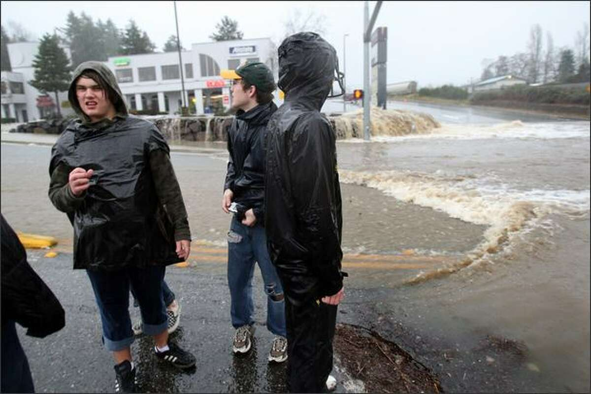 Woodinville High School seniors PJ Petterson, (left) Steven Brey, and Greg Kachmarik try to figure out how they will get home at the intersection of Little Brear Creek Parkway/ NE 177th PL and 131st Ave NE which had severe flooding in Woodinvellie, Wash. on December 3, 2007. The area was devastated by a winter storm. The kids decided to leave their cars at school and walk home because the traffic was so bad.
