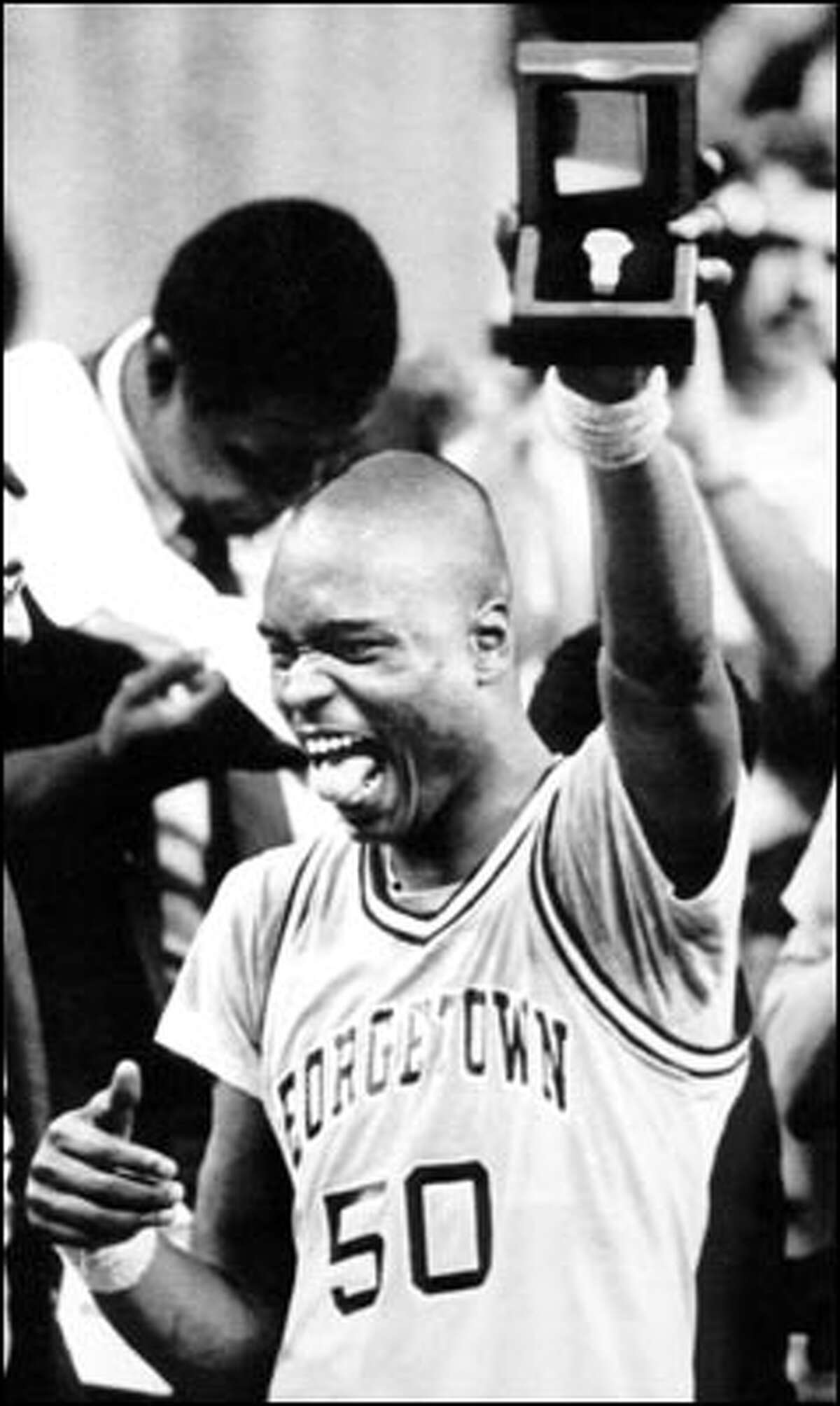 April 3, 1984: Georgetown's Michael Graham holds up the trophy after his team beat Houston to win the NCAA championship in Seattle.