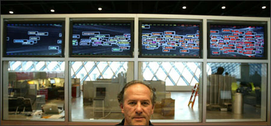"""George Legrady poses with his installation, """"Making Visible the Invisible,"""" at the Seattle Central Library's Mixing Chamber. Photo: Mike Urban/Seattle Post-Intelligencer / Seattle Post-Intelligencer"""