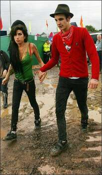 British pop singer Amy Winehouse (L) walks through the mud to the Pyramid stage with an unidentified friend, as she prepares to perform at the Glastonbury music festival, in Pilton, Somerset, in south-west England, June 22, 2007. Winehouse is on Mr. Blackwell's 48th annual worst-dressed list. Photo: Getty Images