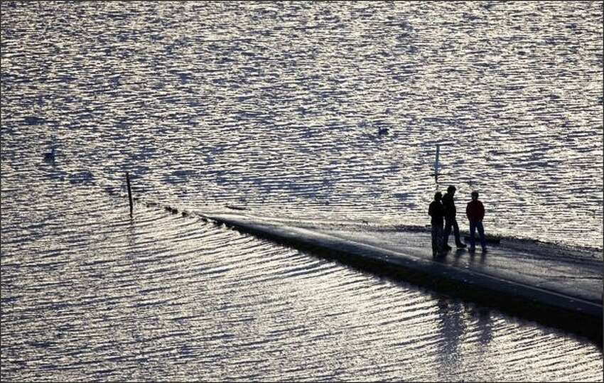 Three people are seen on a ramp on the flooded I-5 freeway in Chehalis on Tuesday.