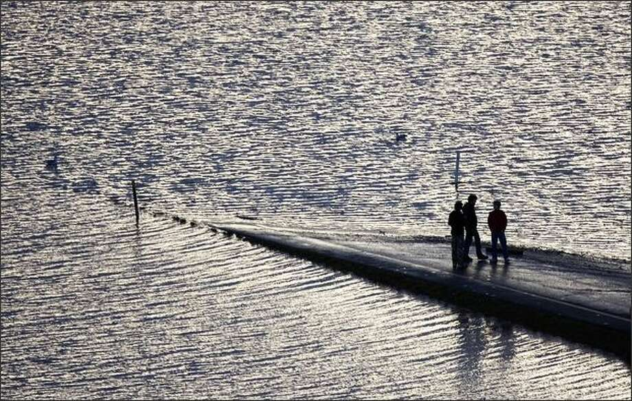 Three people are seen on a ramp on the flooded I-5 freeway in Chehalis on Tuesday. Photo: Associated Press