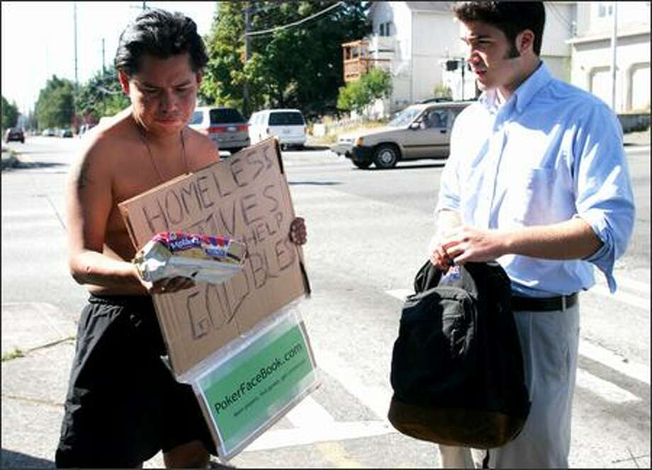 Zack Peters, left, who stood in the University District recently asking for help from passing motorists, received a package of Fig Newtons, $5 and bottled water from Ben Rogovy for holding a sign advertising Rogovy's Internet site. Rogovy's practice of using beggars to advertise has sparked praise and criticism. Photo: NIKI DESAUTELS/P-I