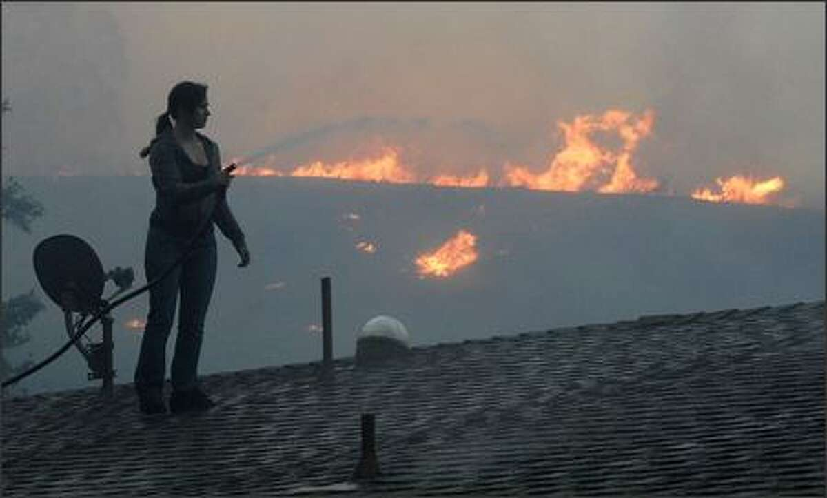 An unidentified woman sprays her roof with water as a fast moving wildfire approaches in Canyon Country, Calif.