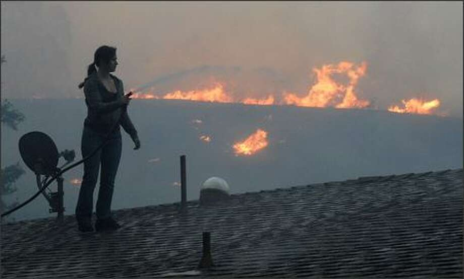 An unidentified woman sprays her roof with water as a fast moving wildfire approaches in Canyon Country, Calif. Photo: Dan Steinberg, Associated Press