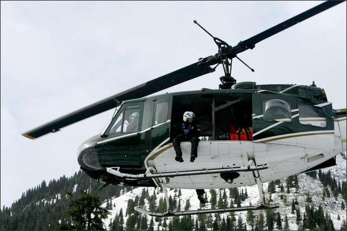 A helicopter from the King County Sherriff's office helps in the search for three missing snowboarders on Crystal Mountain.