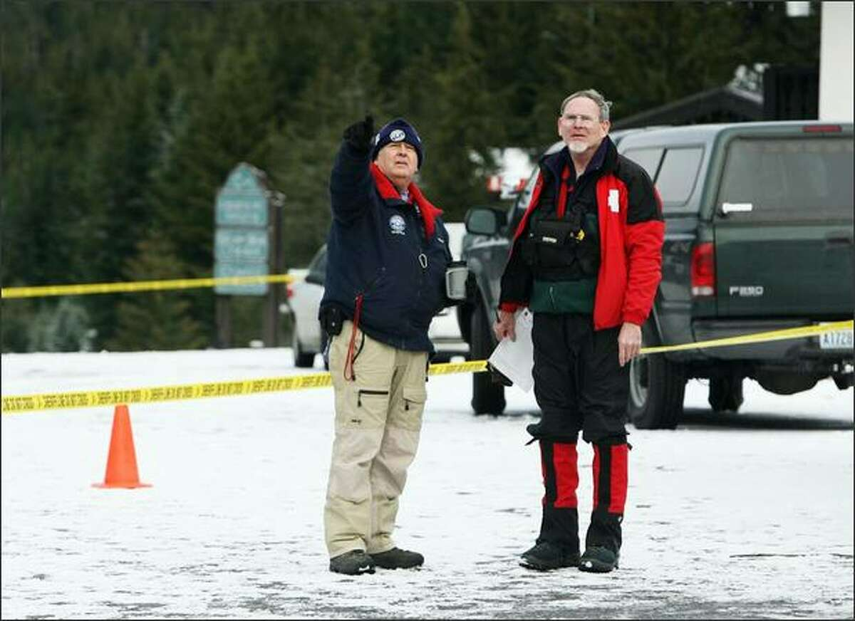 Art Farash, Seattle Mountain Rescue,(left) and Ralph Javins, Ski Patrol Rescue Team King County, look up the mountain from the base camp as the search goes on for three missing snowboarders on Crystal Mountain.