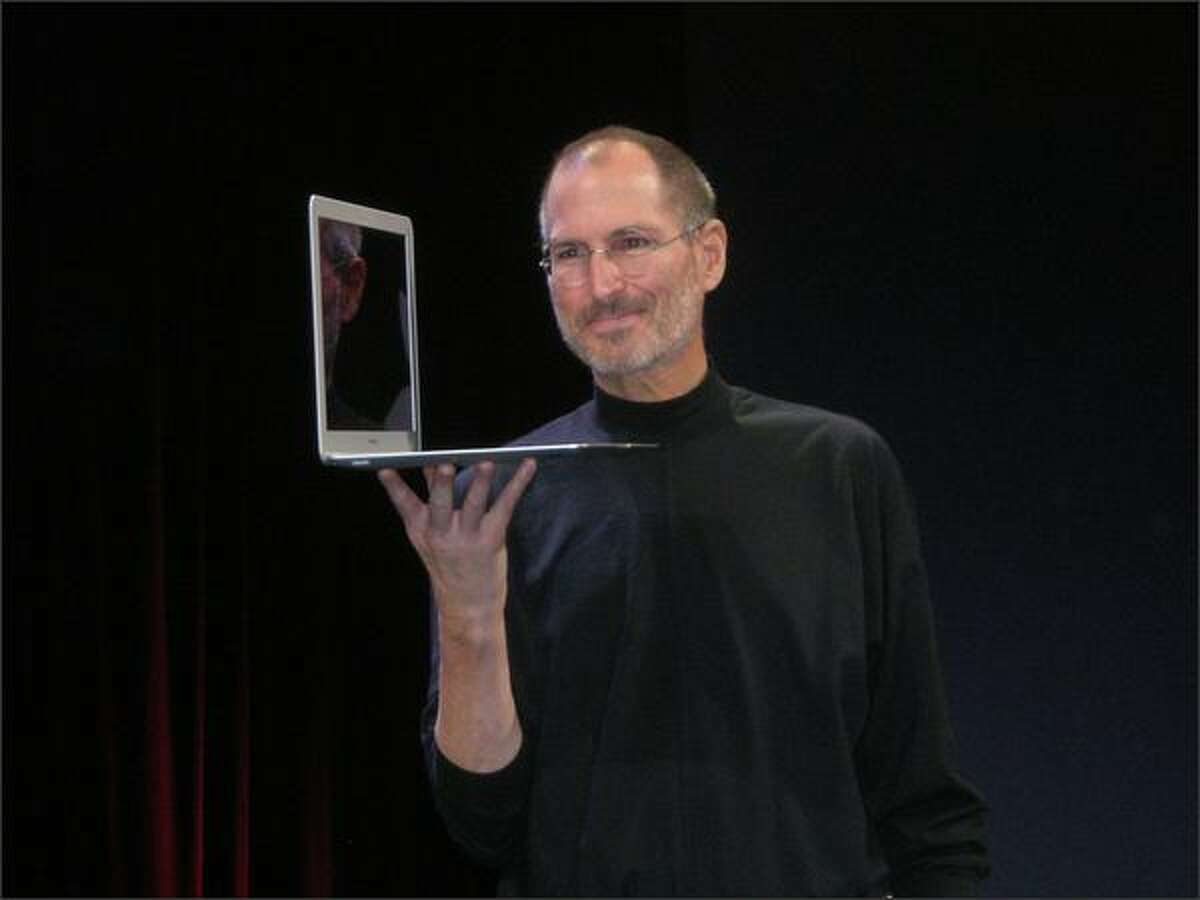Apple CEO Steve Jobs shows off the new MacBook Air: Just 0.16 inches thick at its thinnest.