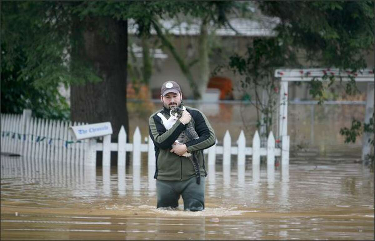Tyler Stanford rescues a cat from his neighbor's home in Centralia on Wednesday.