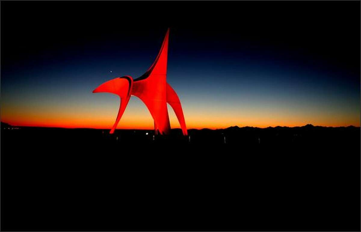 """Just after sunset, the planet Venus is visible over the beak of Alexander Calder's 1971 sculpture """"Eagle"""" at the Seattle Art Museum's Olympic Sculpture Park.Haller: Looking like a primordial monster emerging from the darkness of our society, Alexander Calder's """"Eagle"""" (although I think it looks more like a killer whale escaping the sea) sits on an edge of our city in a place now called the Olympic Sculpture Park. The site used to house huge oil tanks where sludge seeped into the ground, so it's possible to think that statue is trying to free itself."""