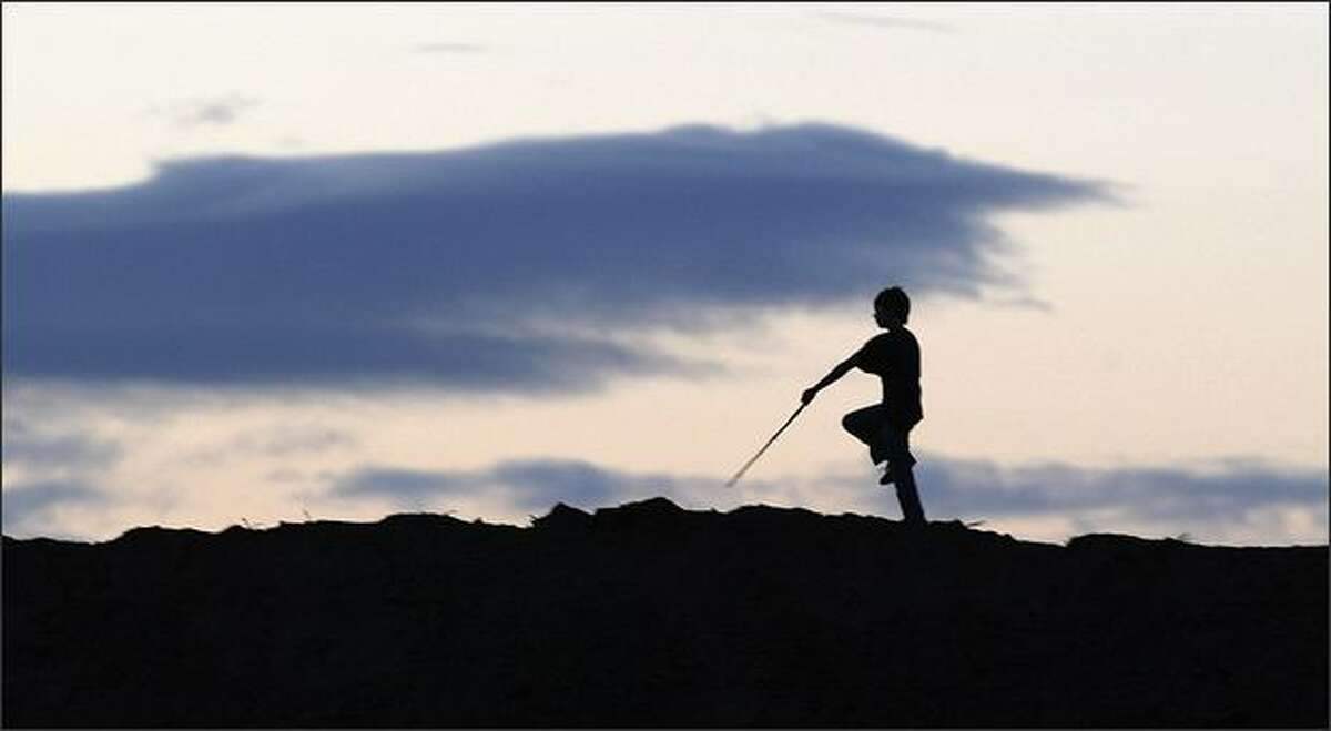 Timothy Reynolds, 11, of Puyallup, marches across a large mound of dirt as he plays with friends recently at a construction site on Puyallup's South Hill. Reynolds said they often play at the site, where the Highlands housing development is being built. On this day they found sticks in the dirt, so they were playing