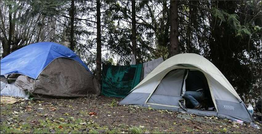A man enters his tent at a homeless encampment located in the hills just north of 1170 Elliott Ave.