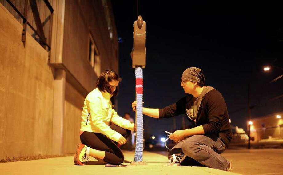 Claudia Rubio (left) and Billy Muñoz wrap a parking meter koozie with yarn for a Contemporary Art Month project by the Yar Dawgz and volunteer knitters. Photo: EDWARD A. ORNELAS, SAN ANTONIO EXPRESS-NEWS / eaornelas@express-news.net